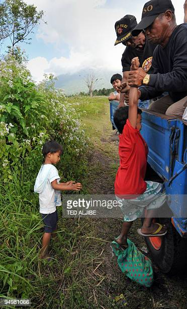 Village watchmen help young residents living in the foothills of the rumbling Mayon volcano get into a truck after local officials asked them to...