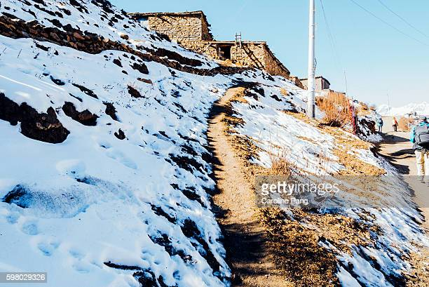 village with snow covered hill slope. - caroline pang stock pictures, royalty-free photos & images