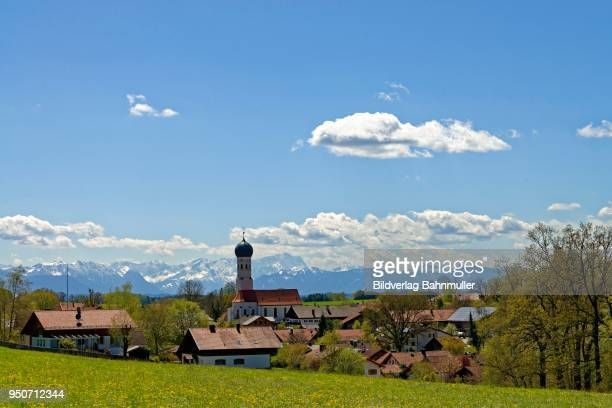 Village with the Parish Church of the Assumption in front of Alps, Wetterstein mountains with Zugspitze, Muensing, Upper Bavaria, Bavaria, Germany