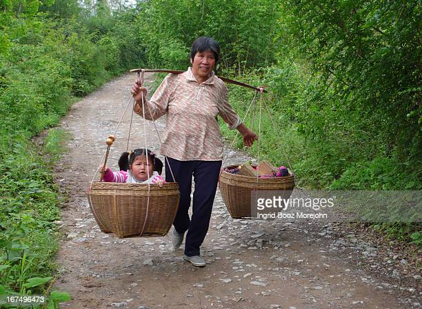 Village woman in countryside carrying her child in a shoulder pole basket counterweighted by souvenirs that she is attempting to sell to tourists.