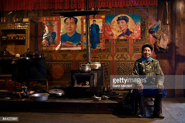 Village woman near the town of Zhongdian, Yunnan Province, China, prepares a meal of yak and rice at the stove of her Tibetan farmhouse with Mao...