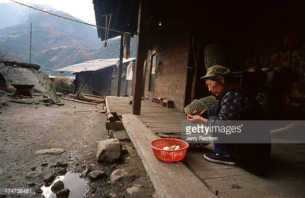 A village woman peels vegetables outside her house in Yong La Ga village which is notched into the hillside several hundred feet above the Nujiang...