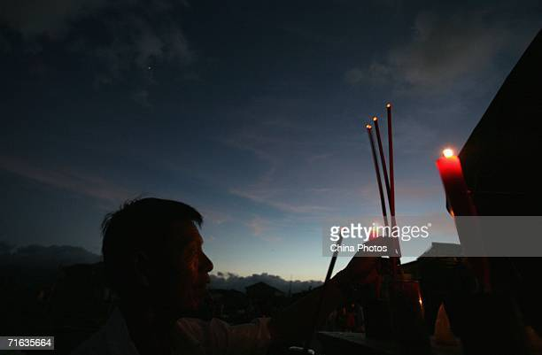 A villager burns incense and mourns relatives killed by typhoon Saomai at Heweiyang Village on August 12 2006 in Cangnan County of Zhejiang Province...