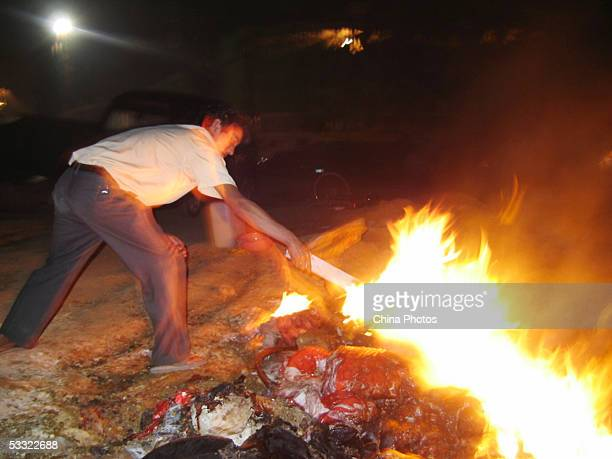 A villager burns spoiled pork at Guanzhuang Village in Guandu District on August 3 2005 in Kunming of Yunnan Province southwest China The village has...