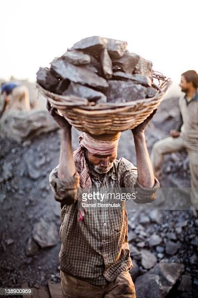 Villager carries a basket of coal scavenged illegally from an open-cast mine in the village of Jina Gora on February 11, 2012 near Jharia, India....