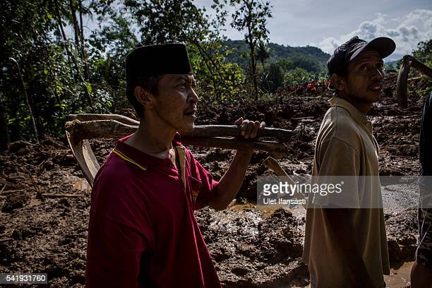 A villager carries a hoe as they prepare search for victims after a landslide at Caok village on June 21 2016 in Purworejo Indonesia At least 47...