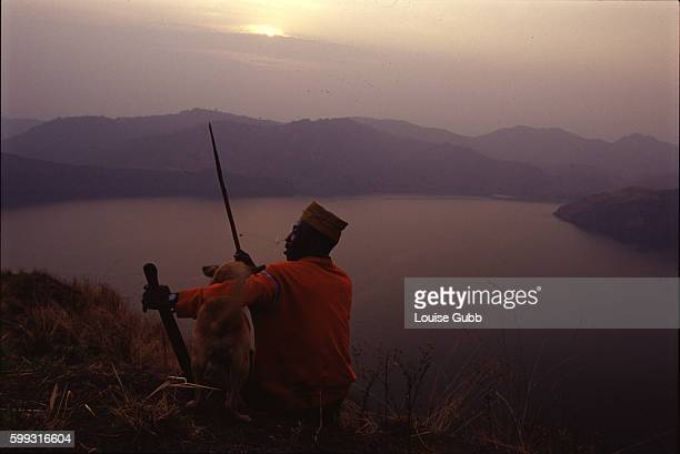 Villager Che Ephriam one of the survivors of the 1986 carbon dioxide gas tragedy sits with Gabon his hunting dog The gas asphyxiated 2000 people when...