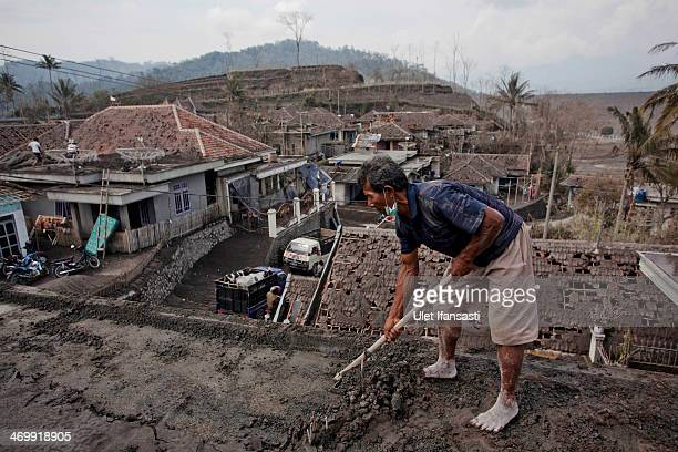 A villager cleans ash from a roof of a damaged house after the eruptions of Mount Kelud at Pandansari village at Pandansari village on February 17...