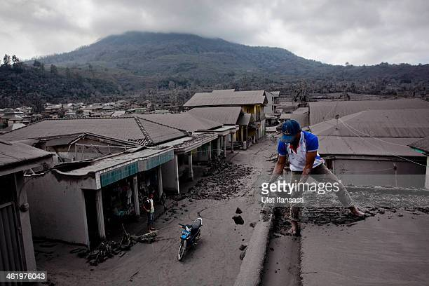 A villager cleans roof his house from ash and mud from eruptions of Mount Sinabung on January 12 2014 in Sigarang Garang village Karo District North...