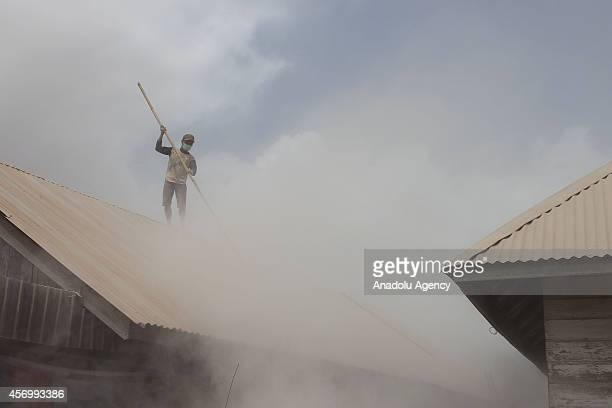 A villager cleans the ashes caused by the eruption of Mount Sinabung volcano at Siroga Ndokum village Karo District North Sumatra Indonesia on...
