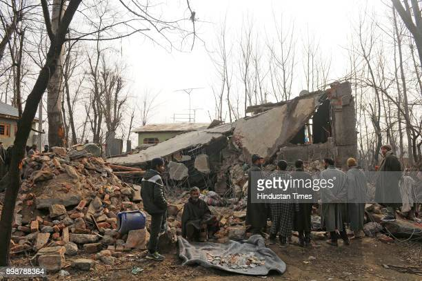 A villager collects money for a residential house which was destroyed during a gunfight at Samboora on December 26 2017 in Pulwama some 30 kilometers...