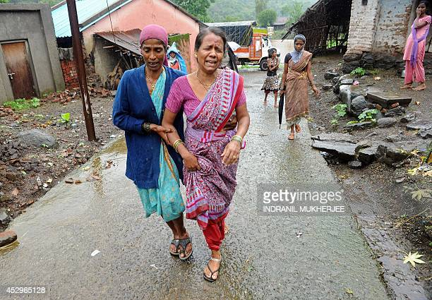 A villager consoles a neighbour who lost her relative following a landslide at Malin village in Pune district of India's western Indian state of...