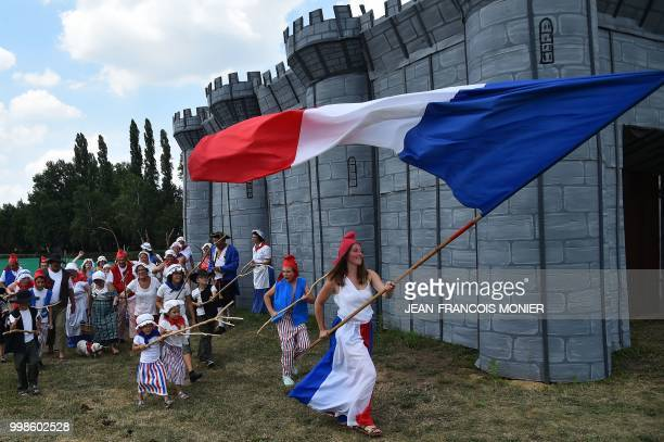 A villager dressed as Marianne personification of the French Revolution performs during Bastille Day celebrations on 14 July 2018 in Lavaré western...