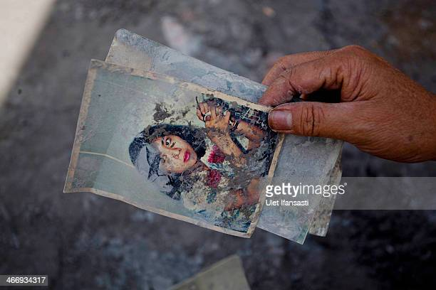 A villager holds a photograph covered by ash while evacuating from a house damaged by ash and mud from the eruptions of Mount Sinabung February 05...