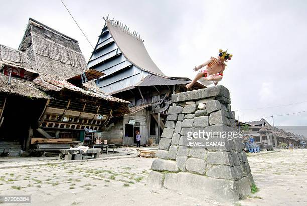 A villager in traditional dress jumps over a stone in front of their ancient houses in Siwahili on Nias island 09 March 2006 More than 200...