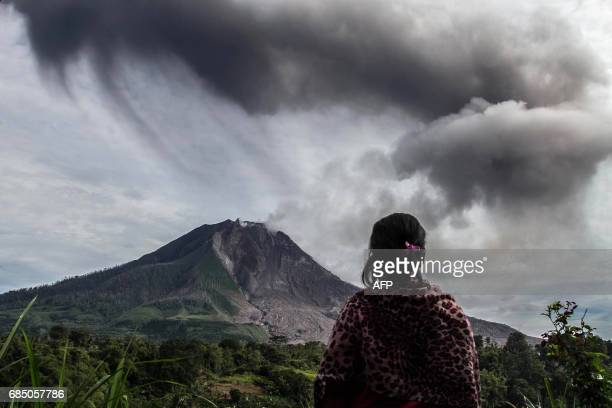 TOPSHOT A villager looks on as Mount Sinabung volcano spews thick volcanic ash as seen from Beganding village in Karo North Sumatra province on May...