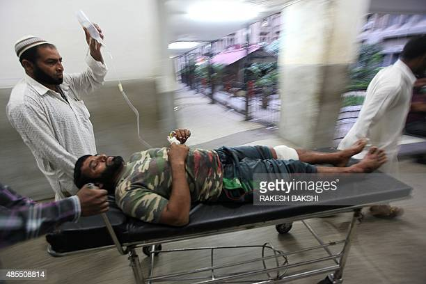 A villager named as Liyakat Ali is transported by medical staff at a hospital in Jammu after he was injured in crossborder firing in...