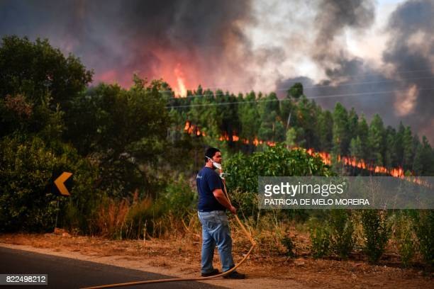 Villager of Sanguinheira carries a hose as a wildfire approaches his house in Macao, central Portugal, on July 25, 2017.