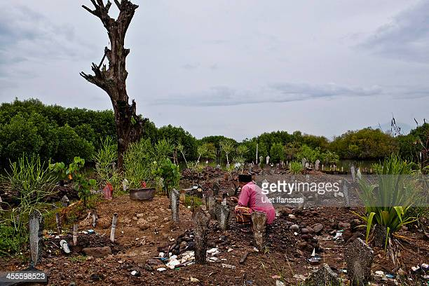 A villager prays at a public cemetery mostly submerged by rising sea levels in Bedono village on December 12 2013 in Demak Central Java Indonesia...