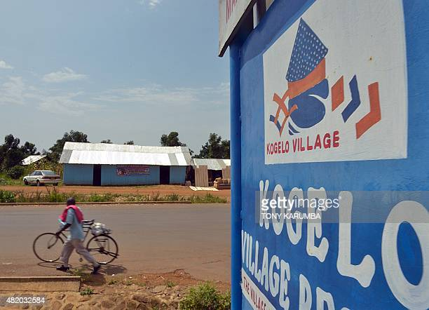 A villager pushes a bicycle past a road sign on Mama Sara Obama Road in the village of Kogelo in Siaya county on July 26 where residents have...