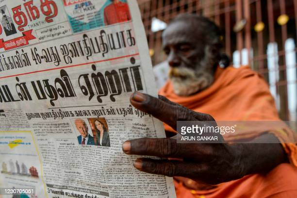 Villager reads a newspaper featuring front-page news on US President Joe Biden and Vice President Kamala Harris in Mannargudi, Tamil Nadu, on January...