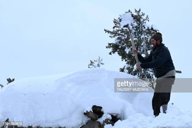 A villager removes snow from a house after a heavy snowfall at Kanidajan area of Budgam district in Srinagar on January 18 2020