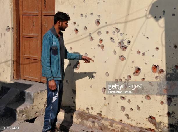 A villager showing the damaged wall of the house due to firing from the Pakistan side of the border at Arnia sector on January 19 2018 in Jammu India...