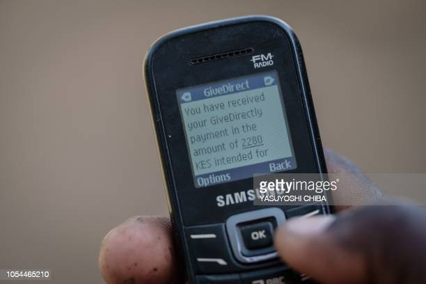 A villager shows his mobile phone's monitor displaying a message confirming the universal basic income transaction250 shillings per month in Bondo...