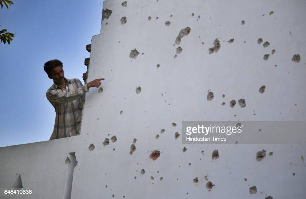 A villager shows the damaged wall of his house after a heavy mortar shelling by Pakistan Rangers on Saturday night at Arnia village on September 17...