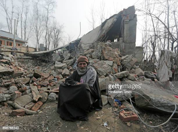 A villager sits infront of a residential house which was destroyed during a gunfight at Samboora on December 26 2017 in Pulwama some 30 kilometers...