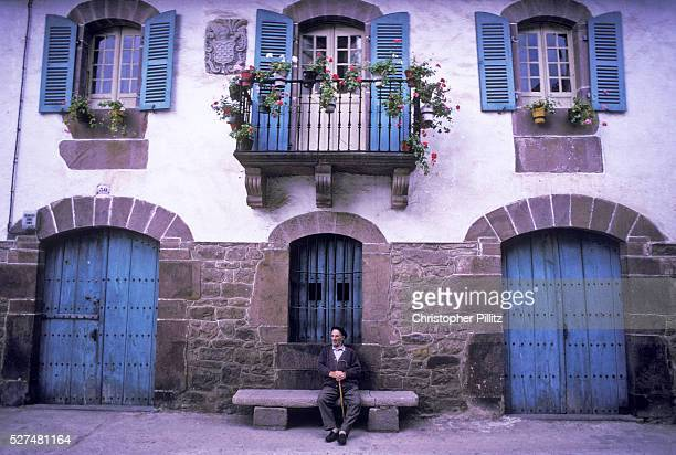 A villager sits on bench infront of house Errazu village Baztan Basque country Spain | Location Errazu Basque Country Spain