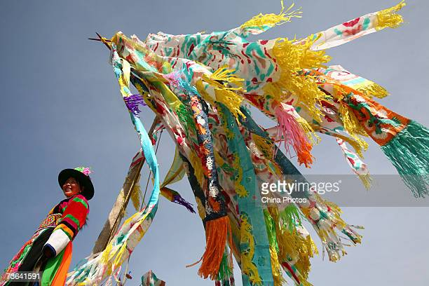 A villager stands below Prayer Flags during a ceremony to worship the Erlang God at the Dazhuang Village on March 20 2007 in Huzhu County of Qinghai...