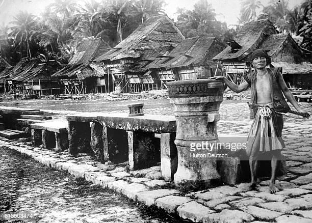 A villager stands beside a row of stone seats in the center of a cobbled square