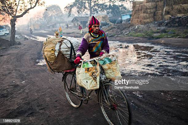 A villager transports coal on a bicycle through the village of Guhanwadi on February 11 2012 near Jharia India Villagers in India's Eastern State of...