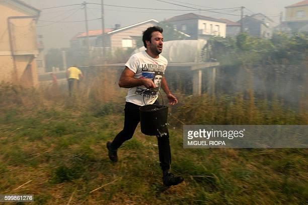 A villager tries to extinguish a fire using a bucket of water in A Illa a village next to Entrimo northwestern Spain on September 7 2016 Thousands of...