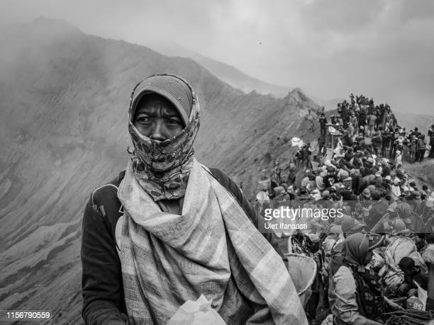 A villager waits to catch offerings thrown by Tenggerese worshippers during the Yadnya Kasada Festival at crater of Mount Bromo on July 18 2019 in...