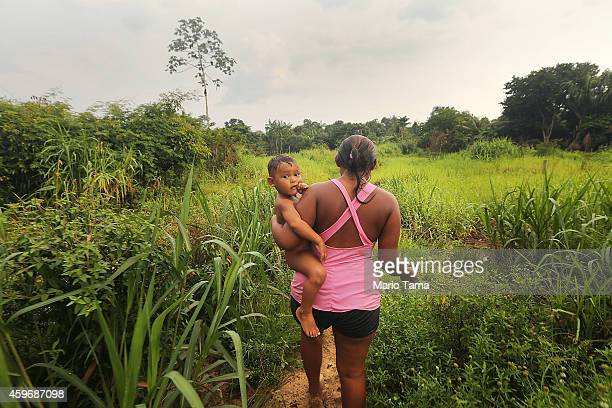 A villager walks with a child to her home near a 'Caravan of Resistance'' protest by indigenous groups and supporters who oppose plans to construct a...