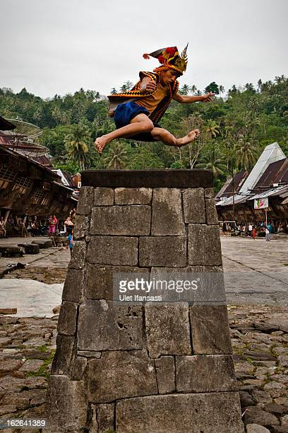 A villager wearing traditional costume jumps over a stone in front of their ancient houses in Orahili Fau village on February 24 2013 in Nias Island...