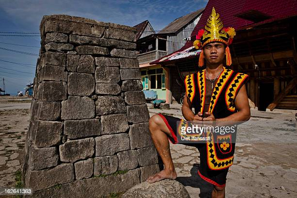 A villager wearing traditional costume poses in front of a stone tower in Bawomataluwo village on February 22 2013 in Nias Island Indonesia Stone...