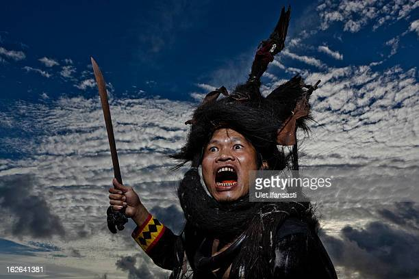 A villager wearing traditional war dress known as leama poses in Bawomataluo village on February 22 2013 in Nias Island Indonesia Stone Jumping is a...