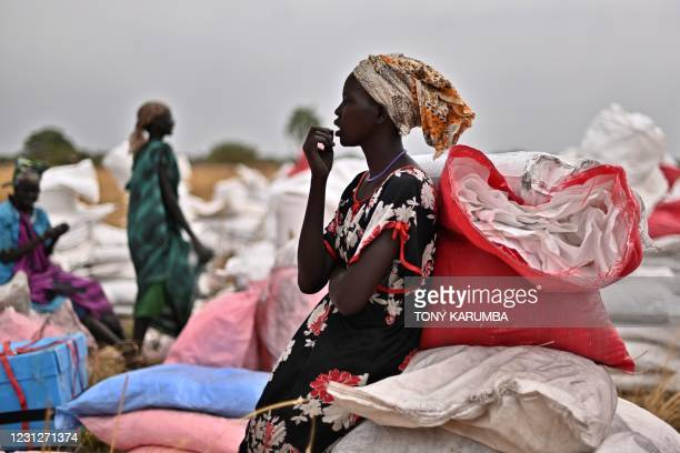 Villager who had volunteered to fetch gunny bags containing food rations from the site of an air drop takes a break at a village in Ayod county,...