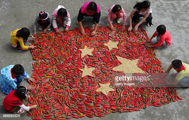 Villager Xie Qiaoying and another villager and students make a fivestar red flag with red chillies at Beiji Village of Zixing City on September 22...