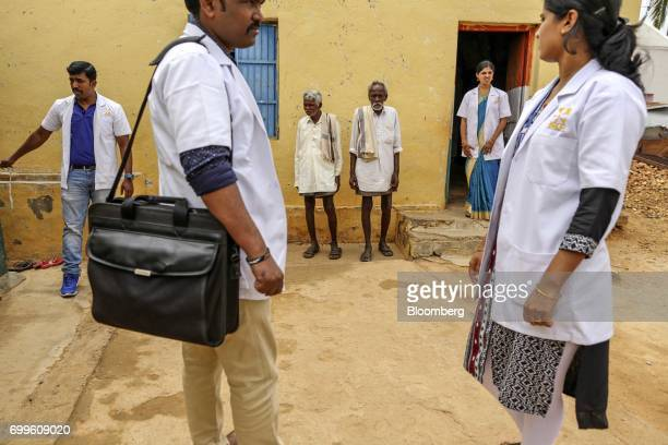 Villagers and medical staff from the Jain Institute of Vascular Sciences stand outside a building in Pancharala on the outskirts of Bengaluru India...
