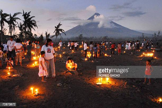 Villagers and survivors offer prayers and candles on Christmas eve 24 December 2006 for victims of the deadly mudslide on the site of Busay village...