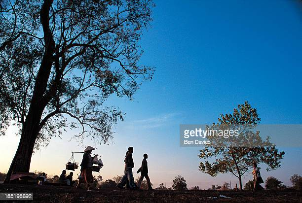 Villagers and vendors walk to the market in the southern Lao province of Champasak in the early morning passing farmers on their way to work Outside...