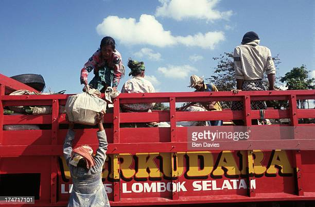 Villagers at Kuta in Lombok Indonesia load up a brightly coloured truck with goods bought at the Sunday Market Like much of Indonesia most produce on...