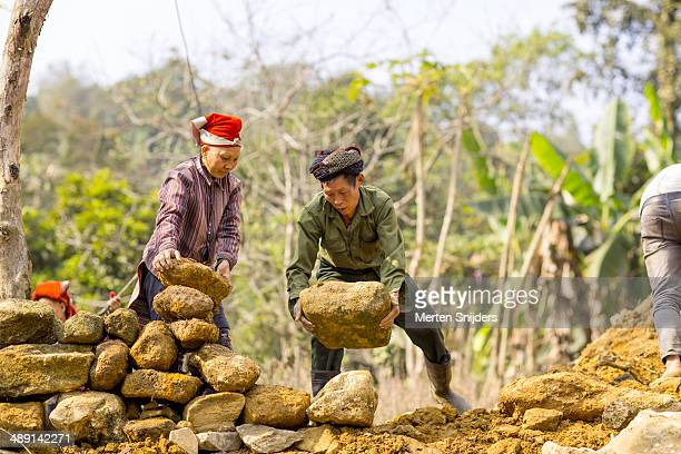 villagers building wall from stones - merten snijders stock pictures, royalty-free photos & images