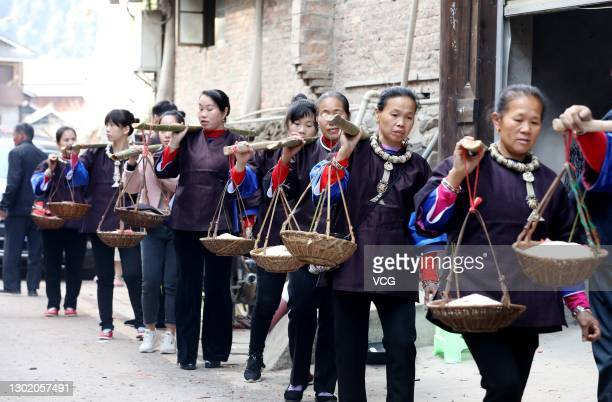 Villagers carry gifts to send outmarried women back to their parents' homes at Sanjiang Dong Autonomous County on February 14, 2021 in Liuzhou,...