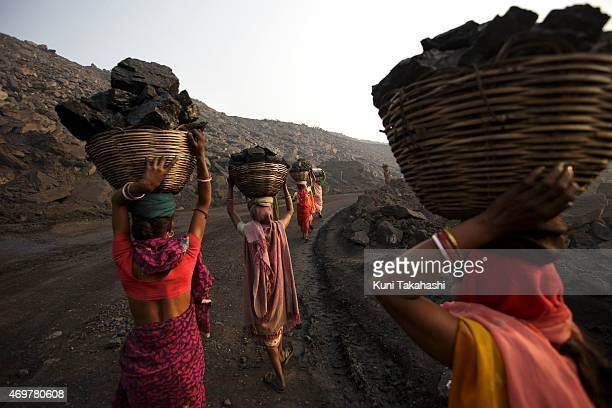 Villagers carry illegally scavenged coal from an opencast coal mine in Dhanbad Jharkhand India on December 6 trying to earn a few dollars a day...