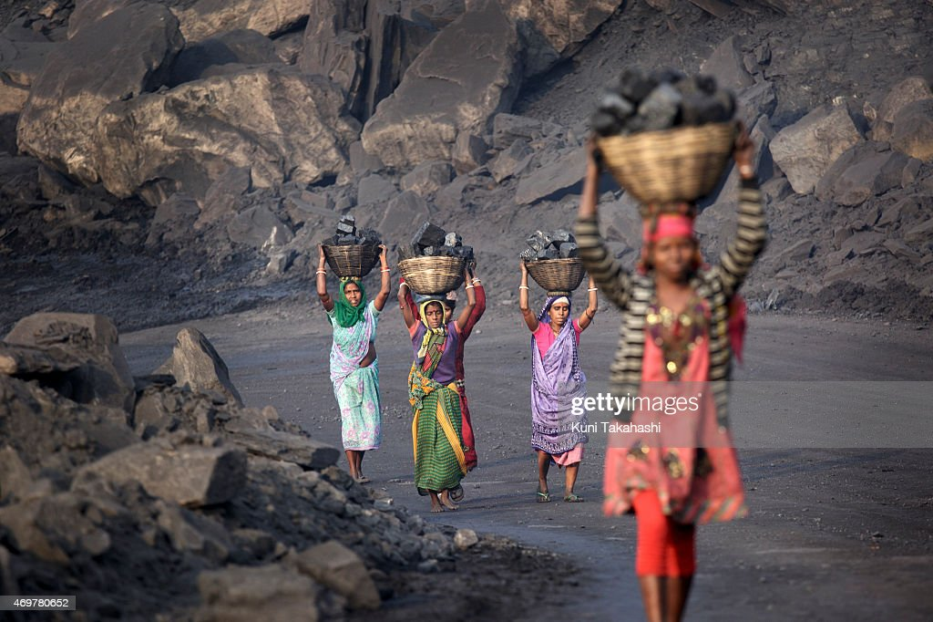 Villagers carry illegally scavenged coal from an open-cast coal mine in Dhanbad, Jharkhand, India on December 6, 2014, trying to earn a few dollars a day. Indian government lead by Prime Minister Narendra Modi plans to double its coal production by 2019.
